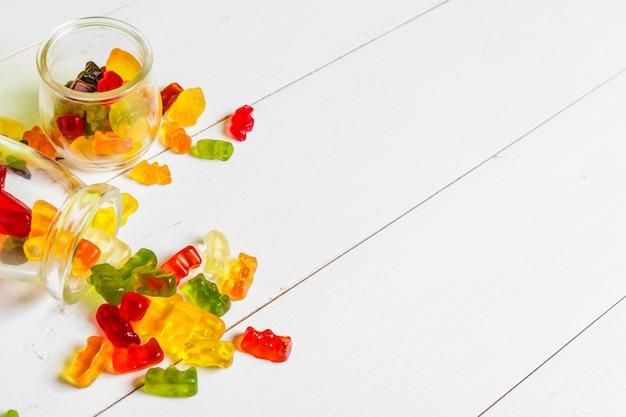 Flaschen mit süßen süßigkeiten auf tabellenhintergrund