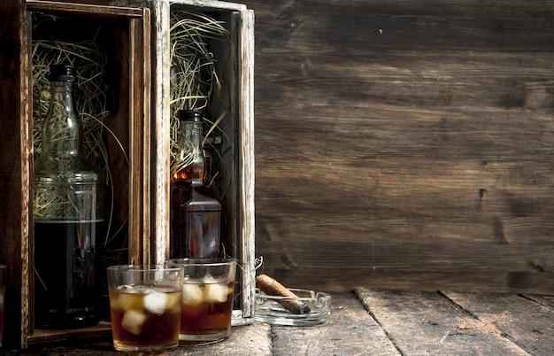 Flaschen mit whisky in alten kisten.
