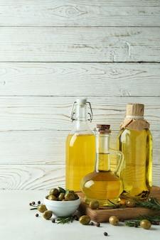 Flaschen olivenöl gegen weiße holzoberfläche
