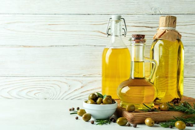Flaschen olivenöl gegen weißen hölzernen hintergrund
