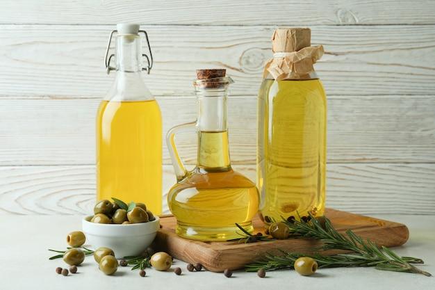 Flaschen olivenöl gegen weißes holz