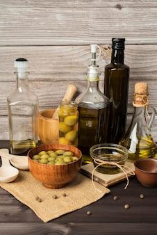 Flaschen olivenöl und oliven auf dem tisch
