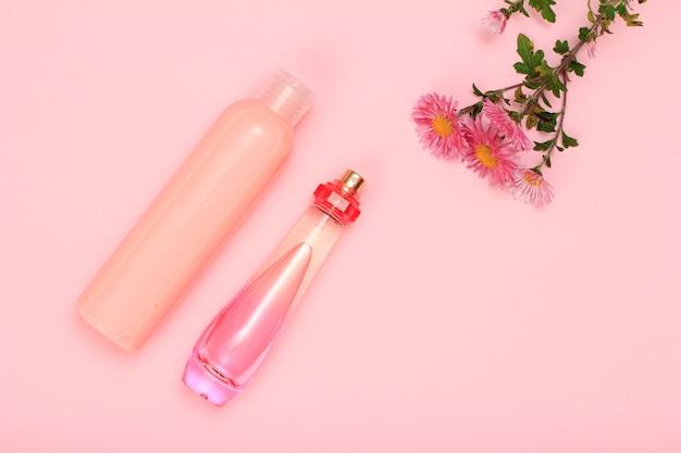 Flaschen parfüm und shampoo auf rosafarbenem hintergrund mit blumen. damenkosmetik und accessoires. ansicht von oben.
