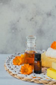 Flaschen ringelblumentinktur oder aufguss und ätherisches öl mit frischen ringelblumenblüten auf einem licht