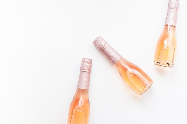 Flaschen rosafarbener champagnerwein auf weißem hintergrund