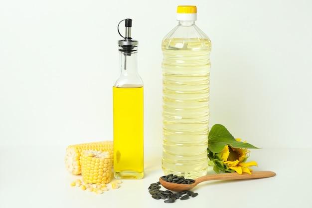 Flaschen sonnenblumen- und maisöl auf weißem hintergrund
