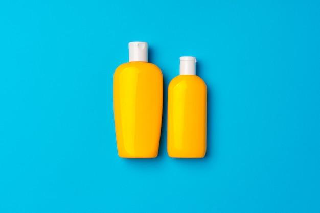 Flaschen sonnenschutzcreme auf blauem hintergrund