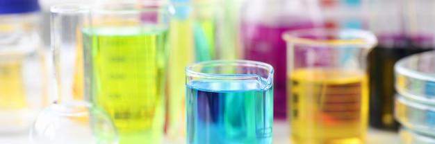 Flaschen und reagenzgläser mit mehrfarbiger flüssigkeit, die in laborchemikalien auf dem tisch steht