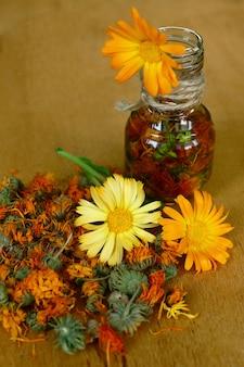 Flaschen und ringelblumen auf holztisch. calendula blüht zu hause rezepte auf dem holztisch.