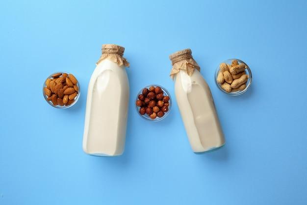 Flaschen vegane milchfreie milch mit verschiedenen nüssen auf blau