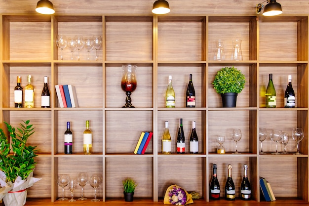 Flaschen weiß- und rotwein auf einem holzregal mit büchern im privaten weingutschrank