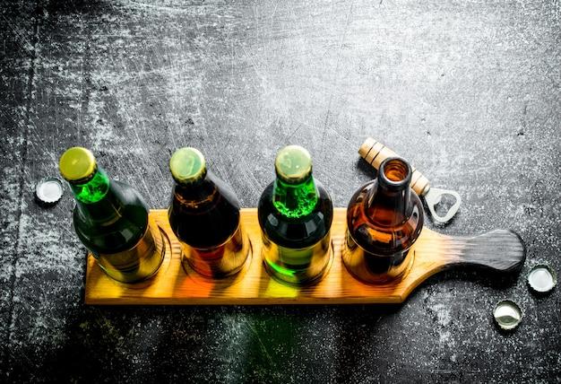 Flaschenbier auf dem stand. auf schwarzem rustikalem tisch