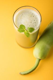 Flaschenkürbis oder lauki-saft ist vorteilhaft für diabetiker- und blutdruckkuren. serviert in einem glas über buntem oder hölzernem hintergrund. selektiver fokus