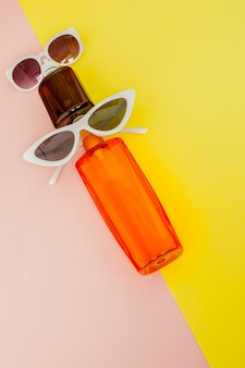 Flaschensonnencreme auf hellem quadratischem gelbem und rosa hintergrund