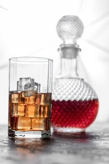 Flaschenwhisky und glas whisky mit eis und licht verwischten hintergrund