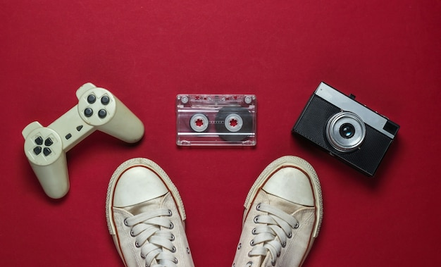 Flat lag altmodische medien und unterhaltung. vvinyl-schallplatte, audiokassette, gamepad, turnschuhe auf rotem hintergrund. 80er jahre. draufsicht