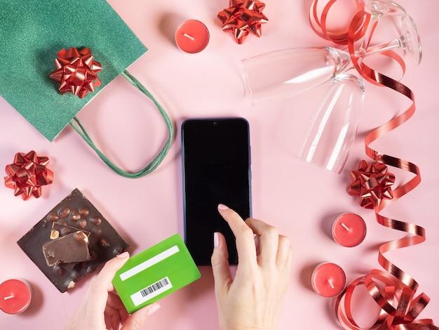 Flat lag online-shopping valentinstag. geschenk, kerzen, gläser, schokolade, bänder auf rosa oberfläche