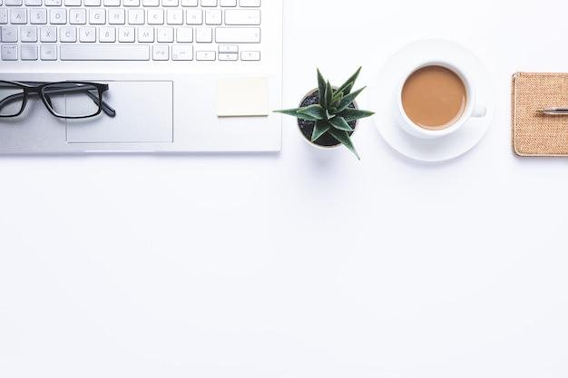 Flat lay, arbeitsplatz mit laptop, kaffee und büromaterial auf dem schreibtisch. mit kopierplatz.