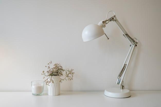 Flat lay, bürotisch schreibtisch mit vorderansicht. arbeitsbereich mit lampe, einer pflanze und kerze auf weißem hintergrund
