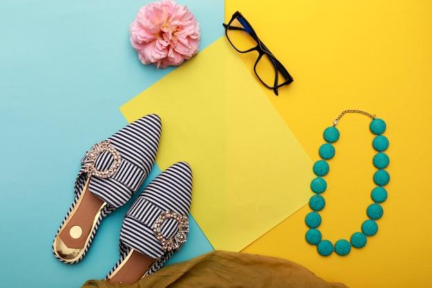 Flat lay fashion set. schuhe mit sonnenbrille auf pastellhintergrund. draufsicht.