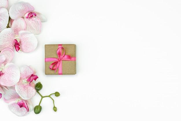 Flat-lay geschenk geschenkbox mit rosa band mit orchideenblumen auf weißem hintergrund draufsicht.