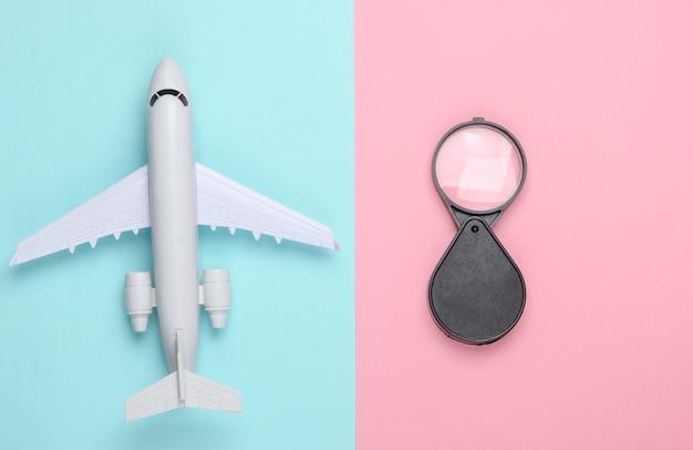 Flat lay reise komposition. flugzeugfigur und lupe auf rosa blauem pastell.