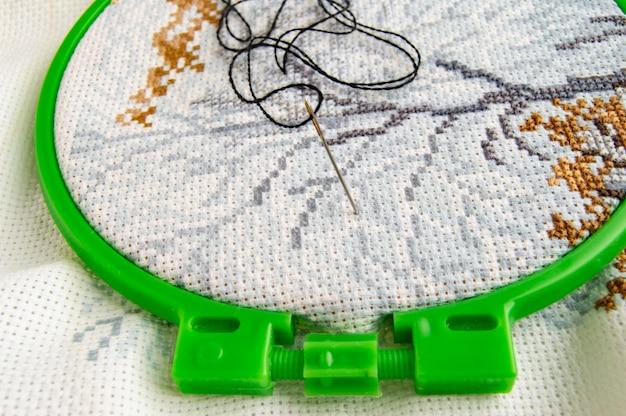 Flat lay stickrahmen mit canvas und hellem nähgarn und sticknadel