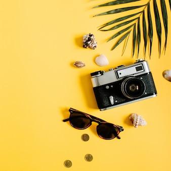 Flat lay traveller accessoires auf gelb mit palmblatt, kamera und sonnenbrille