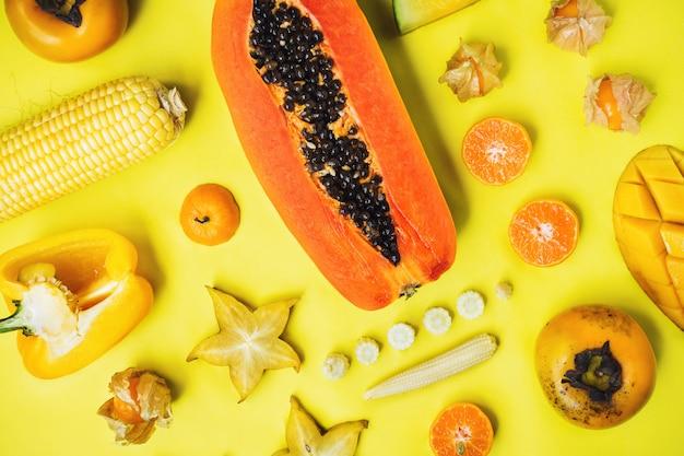 Flatlay aus verschiedenen gelben und orangefarbenen früchten und gemüsen, die zusammen geknöpft sind