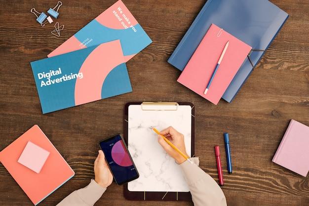 Flatlay der hände des jungen zeitgenössischen vermarkters mit bleistift über leerem papier in der zwischenablage, umgeben von flugblättern oder büchern und notizbüchern