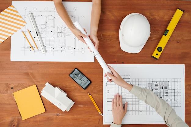 Flatlay der hand der jungen architektur, die gerollte blaupause an kollegen über holztisch mit helm, smartphone und arbeitsmaterial übergibt