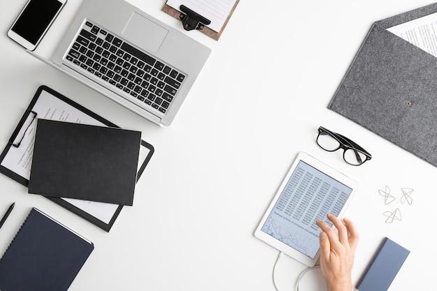 Flatlay der hand des zeitgenössischen ökonomen unter verwendung des tablets beim analysieren von finanzdaten zwischen laptop, dokumenten in der zwischenablage und so weiter