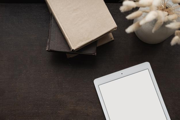 Flatlay der leeren bildschirmtablette, flauschiges hasenhasenmärchengras auf braunem hintergrund. schreibtischarbeitsplatz