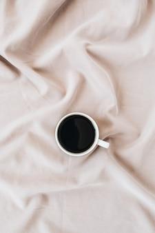 Flatlay der schwarzen kaffeetasse auf pastellrosa decke