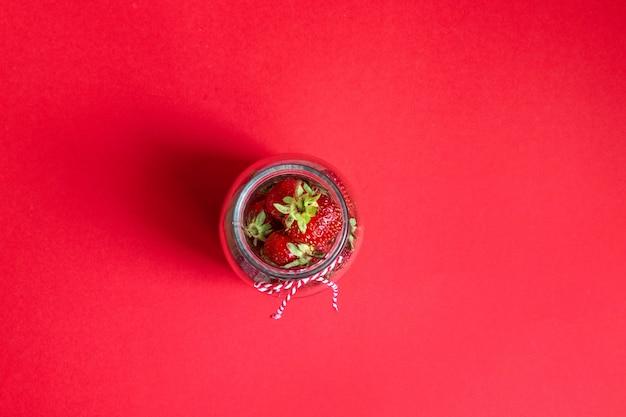 Flatlay-komposition ein glas auf rotem hintergrund für artikel, poster und infografik.