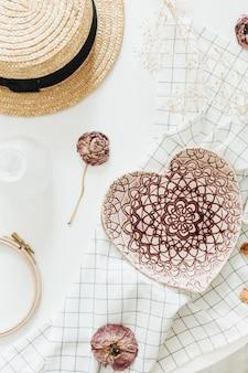 Flatlay-komposition mit rosa handgemachtem herzförmigen teller auf decke, rosenblume und strohhut auf weißer oberfläche. flache lage, draufsicht