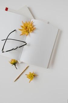 Flatlay leeres papierblatt, notizbücher, gläser, blütenknospen auf weißem hintergrund. flache lage, draufsicht.