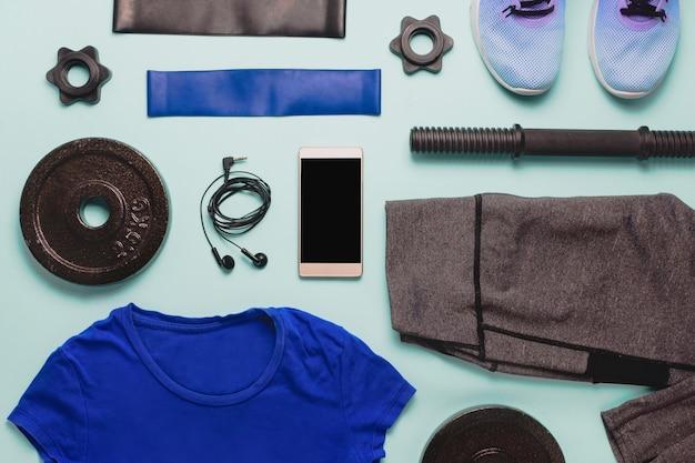 Flatlay mit verschiedenen sportzubehörteilen: trainingsschuhe, leggins, widerstandsbänder, gewichte und smartphone mit schwarzem copyspace. draufsicht.
