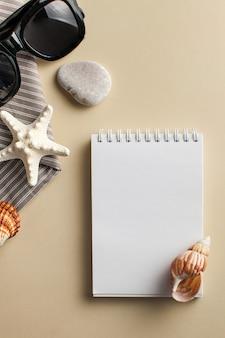 Flatlay mit weißem notizbuch, muscheln, sonnenbrille