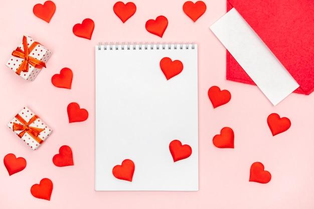 Flatlay-notizblock mit einem roten umschlag mit herzen und geschenken auf einem rosa hintergrund. konzept des valentinstags und des schreibens von liebesbriefen