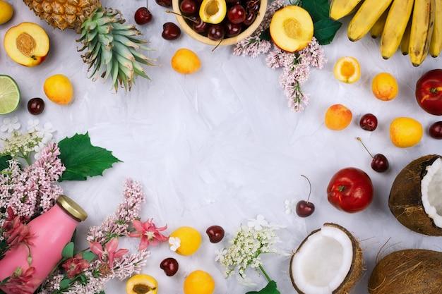 Flatlay-rahmenanordnung mit verschiedenen bio-früchten: bananen, kokosnüsse, ananas, pfirsiche, frische kirschen, lila blumen und smoothie-flasche auf grauem zementhintergrund mit copyspace