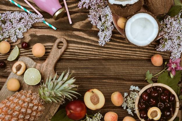 Flatlay rahmenanordnung mit verschiedenen früchten und blumen auf holztisch