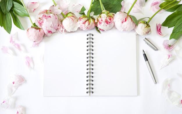 Flatlay-schreibtisch arbeitsplatz mit pfingstrosenblüten und blocknotiz schreibkonzept planen