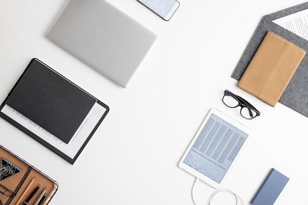 Flatlay tablet, dokumente in zwischenablage, mehrere notizbücher in lederhülle, brille, smartphone, umschlag mit papier und büromaterial