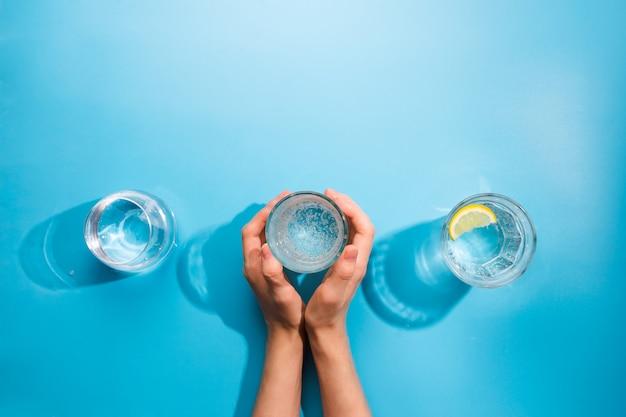 Flatlay von frauenhänden, die eine tasse sauberes sprudelwasser halten. gesundes konzept, blauer hintergrund
