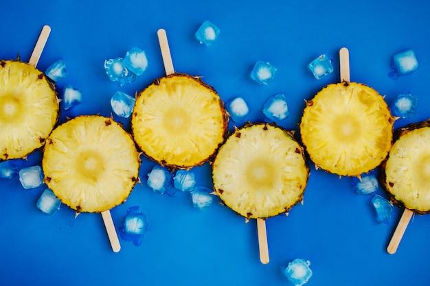 Flatlay von geschnittenen ananas auf hölzernen eis am stiel mit eiswürfeln auf blauem hintergrund