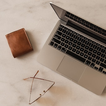 Flatlay von laptop, geldbörse, brille auf marmortisch. arbeitsplatz im homeoffice