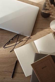 Flatlay von laptop, notebook, brille auf holzhintergrund. home-office-arbeitsplatz im sonnenlichtschatten