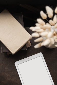 Flatlay von leerem bildschirmtablett, büchern, flauschigem hasengras auf braun