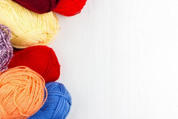 Flatlay von mehrfarbigen strickenden pastellsträngen des garns und der stricknadeln auf weißem hintergrund